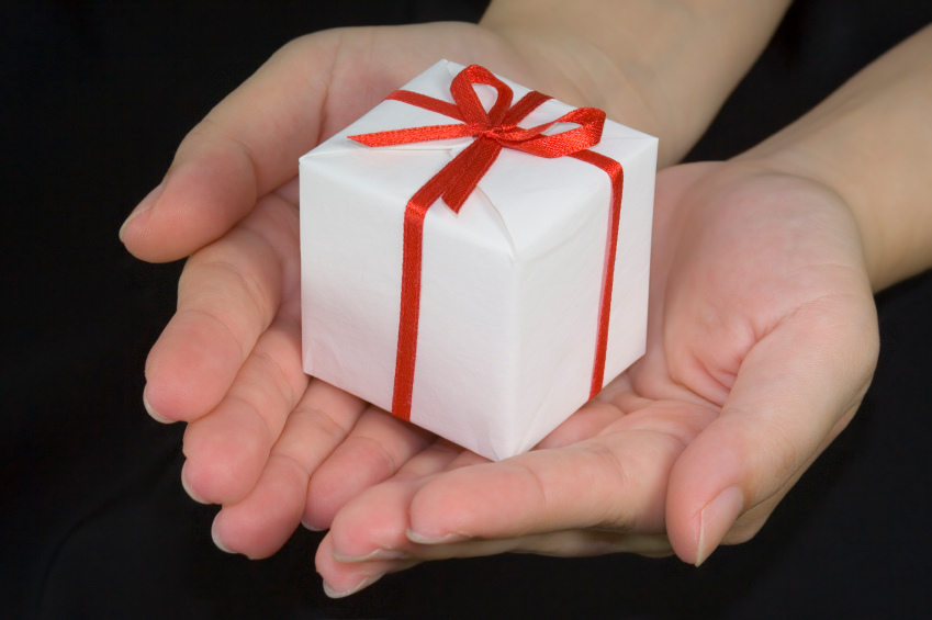 two hands hold small white box wrapped with red ribbon