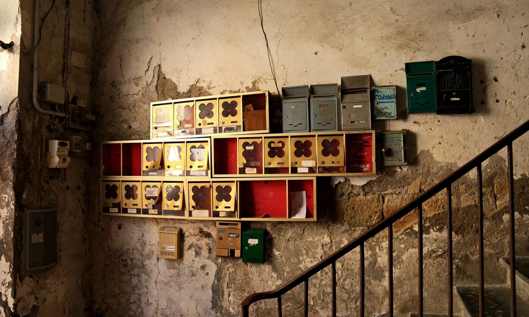 tin mail boxes bunched together on a wall with a set of stairs by the side in an amber lit room