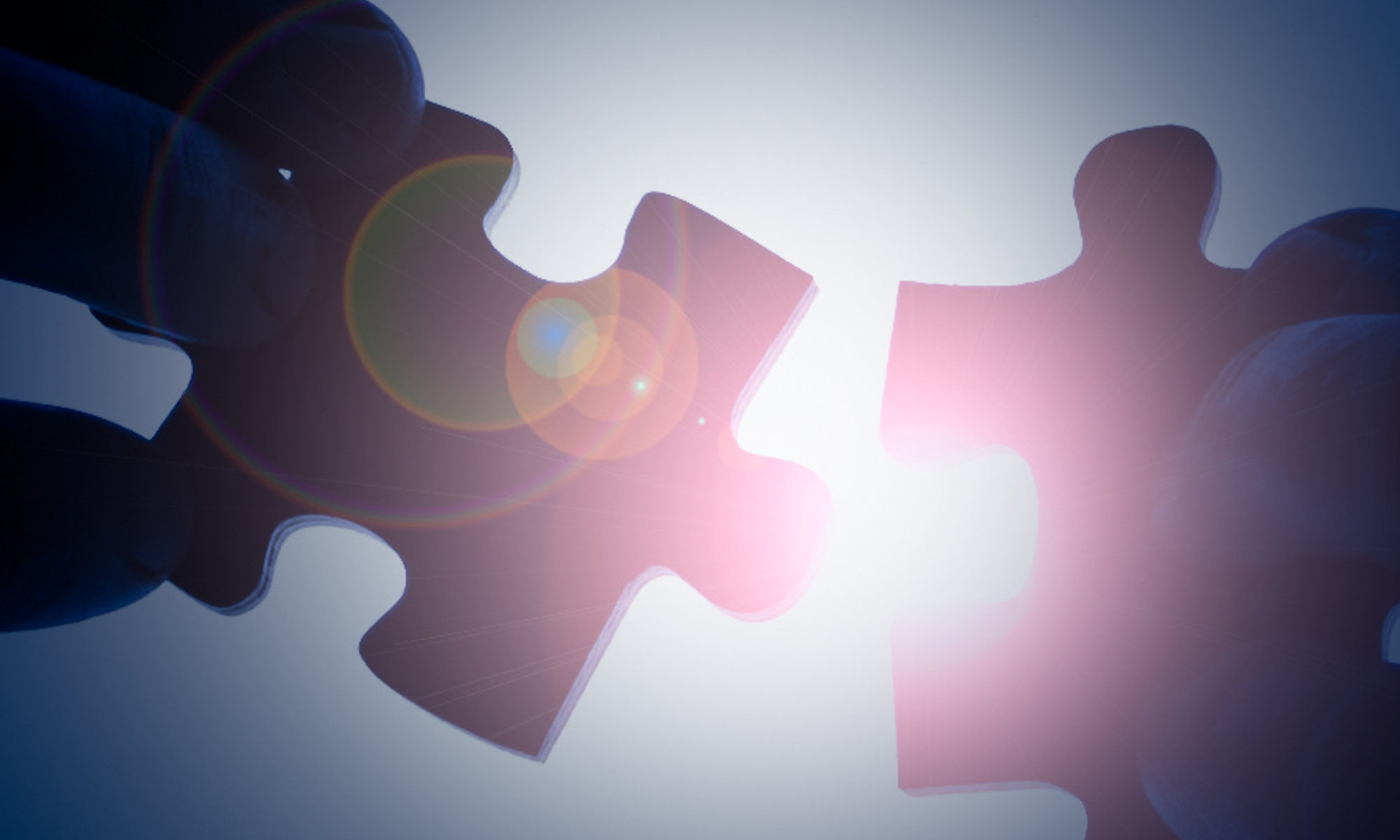 light glares down between two opposing puzzle pieces